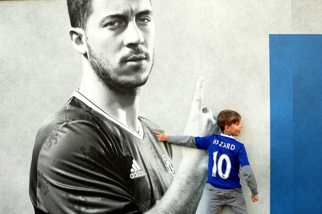 LONDON, ENGLAND - DECEMBER 26: A young Chelsea supporter stands infront of a Eden Hazard poster outside the stadium prior to the Premier League match between Chelsea and AFC Bournemouth at Stamford Bridge on December 26, 2016 in London, England. (Photo by Jordan Mansfield/Getty Images)