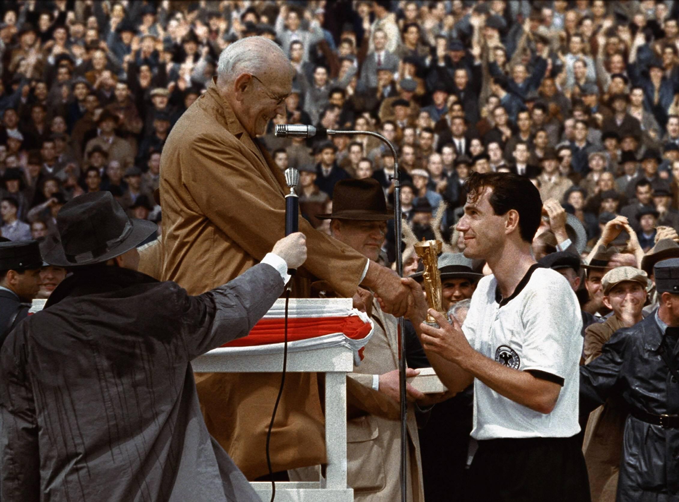 """Spielszene aus dem Film """"Das Wunder von Bern"""" mit Knut Hartwig als Fritz Walter (BRD), der den Pokal entgegen nimmt."""