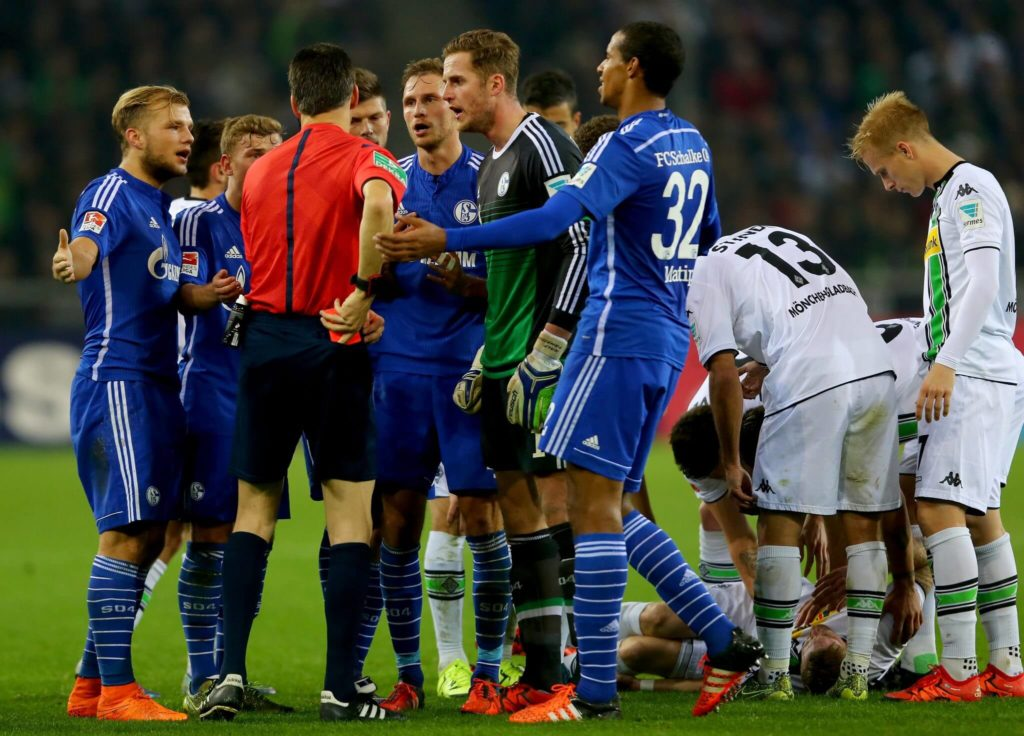 MOENCHENGLADBACH, GERMANY - OCTOBER 25: The team of Schalke talks to referee Wolfgang Stark after givven Johannes Geis s0 (L) the red card during the Bundesliga match between Borussia Moenchengladbach and FC Schalke 04 at Borussia-Park on October 25, 2015 in Moenchengladbach, Germany. (Photo by Christof Koepsel/Bongarts/Getty Images)