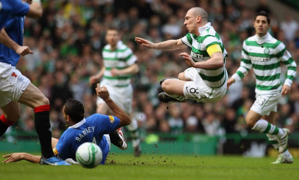 GLASGOW, SCOTLAND - FEBRUARY 20: Scott Brown of Celtic is tackled by Kyle Bartley of Rangers during the Clydesdale Bank Premier League match between Celtic and Rangers at Celtic Park on February 20, 2011 in Glasgow, Scotland.. (Photo by Jeff J Mitchell/Getty Images)