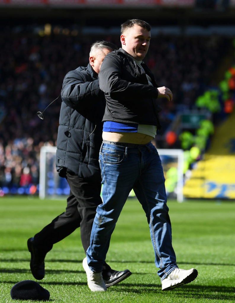 BIRMINGHAM, ENGLAND - MARCH 10: A fan is escorted off the pitch after striking Jack Grealish of Aston Villa during the Sky Bet Championship match between Birmingham City and Aston Villa at St Andrew's Trillion Trophy Stadium on March 10, 2019 in Birmingham, England.