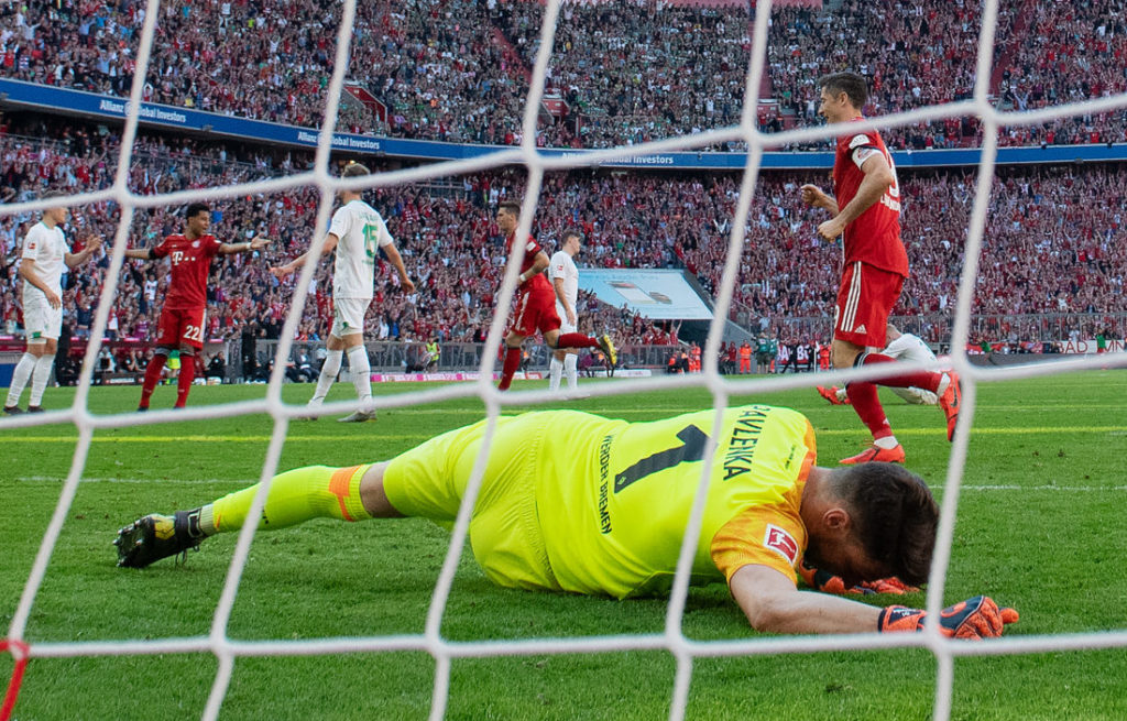 MUNICH, GERMANY - APRIL 20: Niklas Suele of FC Bayern Muenchen scores his team's first goal past goalkeeper Jiri Pavlenka of Bremen during the Bundesliga match between FC Bayern Muenchen and SV Werder Bremen at Allianz Arena on April 20, 2019 in Munich, Germany.