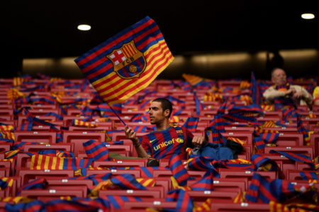 MADRID, SPAIN - APRIL 21: A Barcelona fan sits and waves his flag ahead of the Spanish Copa del Rey match between Barcelona and Sevilla at Wanda Metropolitano on April 21, 2018 in Barcelona.