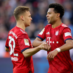 MUNICH, GERMANY - APRIL 06: Serge Gnabry of Muenchen celebrates scoring the 4th goal with his team mate Joshua Kimmich (L) during the Bundesliga match between FC Bayern Muenchen and Borussia Dortmund at Allianz Arena on April 06, 2019 in Munich, Germany.