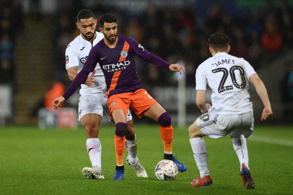 SWANSEA, WALES - MARCH 16: Riyad Mahrez of Manchester City is challenged by Cameron Carter-Vickers of Swansea City during the FA Cup Quarter Final match between Swansea City and Manchester City at Liberty Stadium on March 16, 2019 in Swansea, United Kingdom.