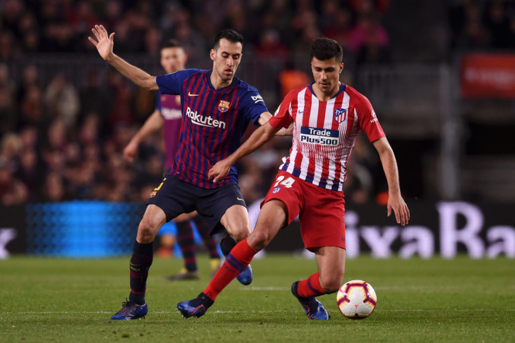 BARCELONA, SPAIN - APRIL 06: Rodri of Atletico Madrid evades Sergio Busquets of Barcelona during the La Liga match between FC Barcelona and Club Atletico de Madrid at Camp Nou on April 06, 2019 in Barcelona, Spain.