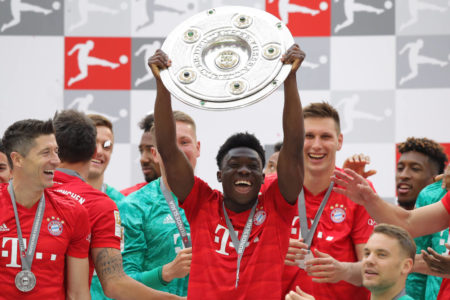 MUNICH, GERMANY - MAY 18: Alphonso Davies of Bayern Munich lifts the trophy following the Bundesliga match between FC Bayern Muenchen and Eintracht Frankfurt at Allianz Arena on May 18, 2019 in Munich, Germany.