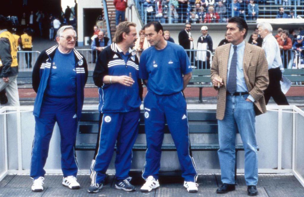 Auf Schalke brauchst du Humor. Wie hier bei Fußball ist unser Leben, Deutschland 2000, Regie: Tomy Wigand. Charly Neumann, Huub Stevens und Rudi Assauer (v. l.) erhalten von Schauspieler Uwe Ochsenknecht (2. v. l.) wohl die letzten Regie-Anweisungen...