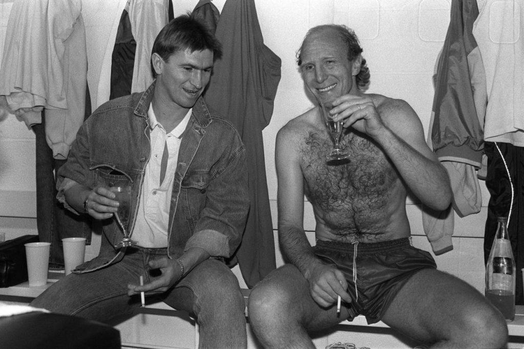 Deutscher Rekordmeister 1987: Klaus Augenthaler (l.) vom FC Bayern München gönnt sich ein Glas Sekt und eine Zigarette. Dieter Hoeneß (r.) raucht aus Sympathie mit.